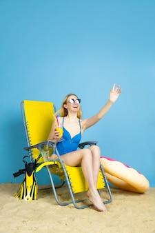 Gelukkige jonge vrouw die met cocktail glimlachen, laughting, groet op blauwe studioachtergrond. concept van menselijke emoties, gezichtsuitdrukking, zomervakantie, weekend. zomer, zee, oceaan, alcohol.