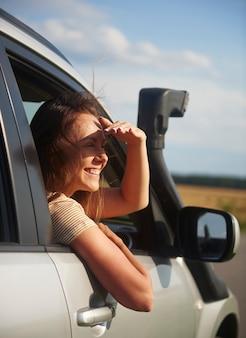 Gelukkige jonge vrouw die met de auto reist en naar het uitzicht kijkt