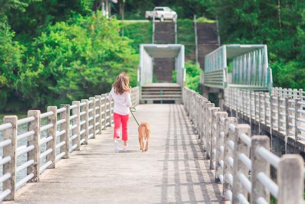 Gelukkige jonge vrouw die met hond in park, gelukkig paar met hond aanstoot die op brug loopt