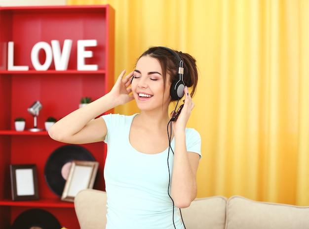 Gelukkige jonge vrouw die met hoofdtelefoons aan muziek thuis luistert
