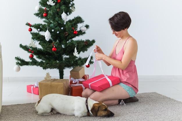 Gelukkige jonge vrouw die met mooie hond huidige doos onder de kerstboom opent