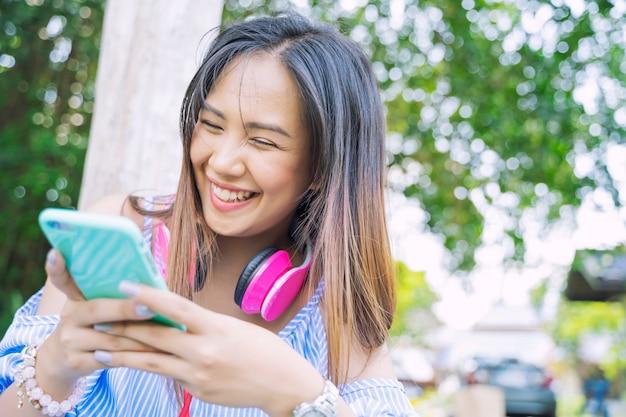 Gelukkige jonge vrouw die mobiele en het luisteren muziek in park met glimlach gebruiken.