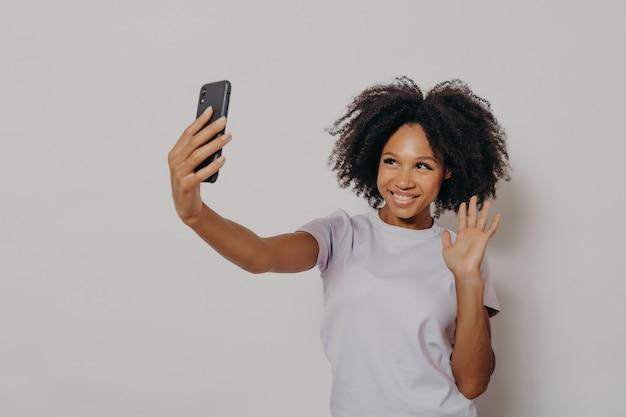 Gelukkige jonge vrouw die naar de camera zwaait terwijl ze videogesprek voert met de beste vriend op moderne smartphone, jonge vrolijke afrikaanse vrouw die positiviteit uitdrukt terwijl ze praat met volgers op sociale media