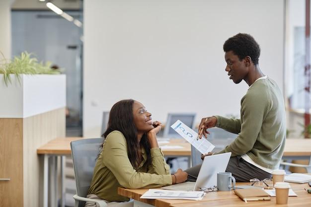 Gelukkige jonge vrouw die naar een collega kijkt die op tafel zit en zijn creatieve innovatieve bedrijf uitlegt...
