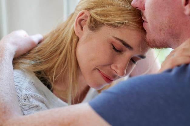 Gelukkige jonge vrouw die ogen sluit en geniet van vriendje die haar op het voorhoofd kust