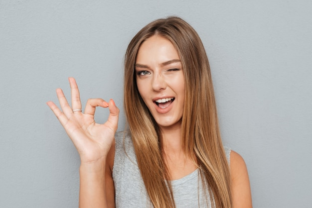 Gelukkige jonge vrouw die ok teken met vingers toont een knipogen geïsoleerd op een grijze achtergrond