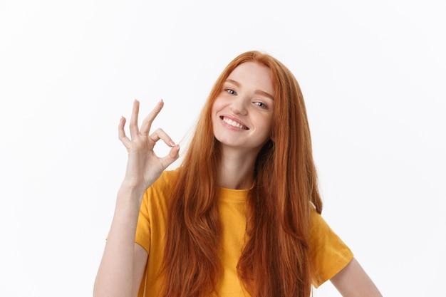 Gelukkige jonge vrouw die ok teken met vingers toont het knipogen