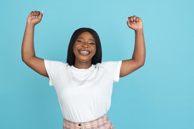 Gelukkige jonge vrouw die op blauwe studiomuur wordt geïsoleerd