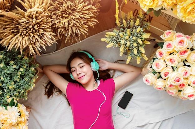 Gelukkige jonge vrouw die op de vloer aan het luisteren muziek via slimme telefoon leggen, hoogste mening