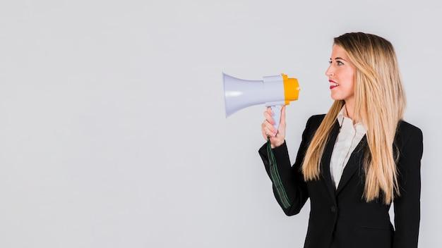 Gelukkige jonge vrouw die op megafoon tegen grijze achtergrond schreeuwt