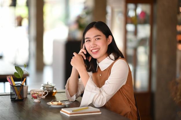 Gelukkige jonge vrouw die op mobiele telefoon spreekt en kijkt