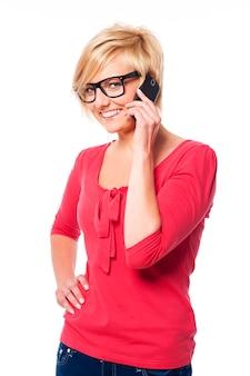 Gelukkige jonge vrouw die op mobiele telefoon spreekt