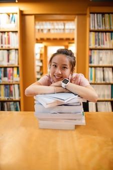 Gelukkige jonge vrouw die op stapel van boek leunt