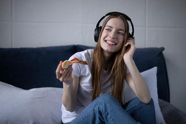 Gelukkige jonge vrouw die plak van hete pizza thuis eet en film op laptop bekijkt