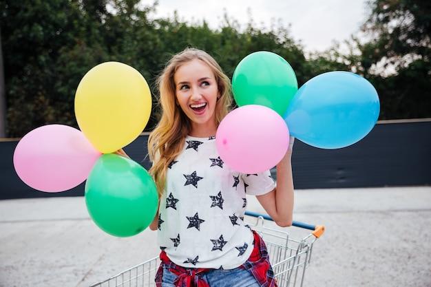 Gelukkige jonge vrouw die plezier heeft met kleurrijke latexballonnen buitenshuis