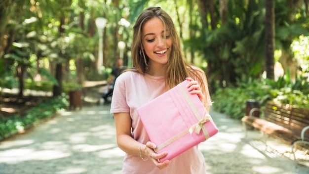 Gelukkige jonge vrouw die roze giftdoos in park houdt