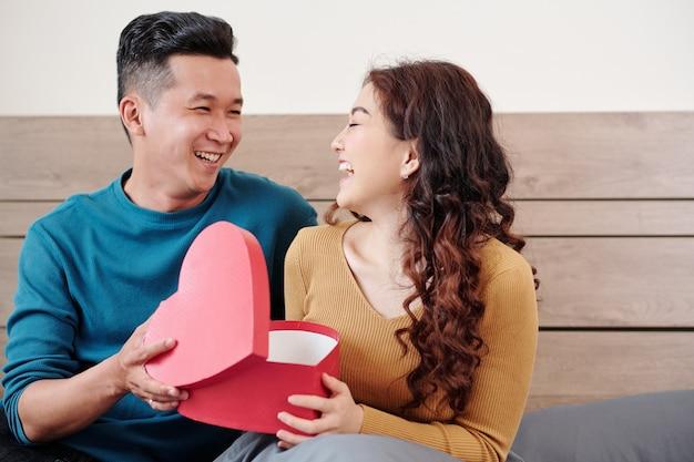 Gelukkige jonge vrouw die 's morgens op bed zit in een hartvormige doos van haar vriendje