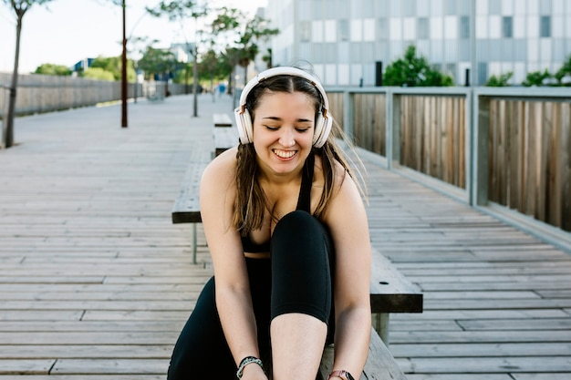 Gelukkige jonge vrouw die schoenveters bindt en zich klaarmaakt voor routinetraining