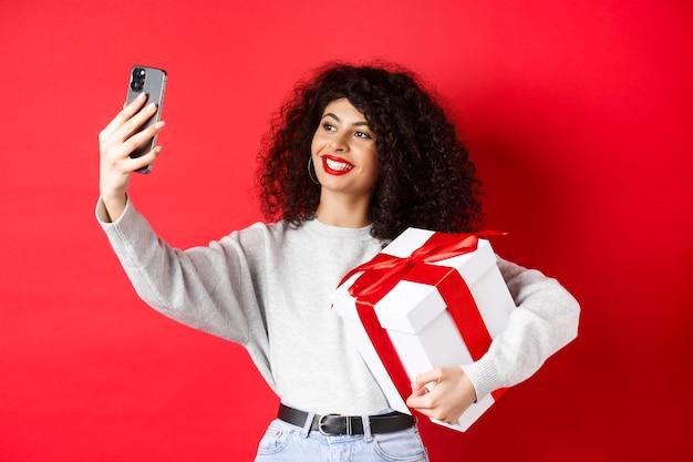 Gelukkige jonge vrouw die selfie neemt met haar valentijnsdagcadeau, heden vasthoudt en fotografeert op smartphone, poserend op rode achtergrond.
