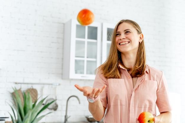 Gelukkige jonge vrouw die sinaasappelen op keukenachtergrond aanstoot