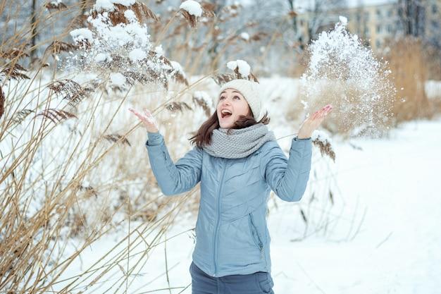 Gelukkige jonge vrouw die sneeuw in lucht in zonnige de winterdag overgeven