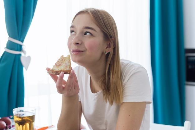 Gelukkige jonge vrouw die thuis een stuk hete pizza eet en geniet van een heerlijke maaltijd.
