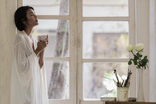 Gelukkige jonge vrouw die thuis zich dichtbij venster het ontspannen in haar woonkamer bevindt en een kop van koffie drinkt.
