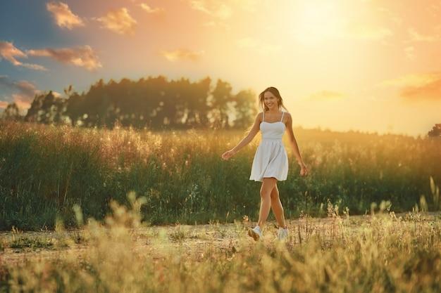 Gelukkige jonge vrouw die tijdens zonsondergang langs landweg in de weide loopt