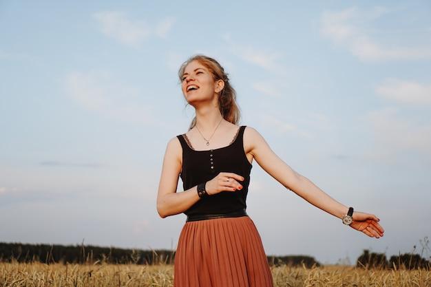 Gelukkige jonge vrouw die van aard en zonlicht op strogebied geniet