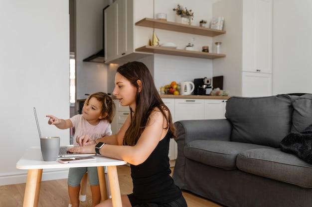 Gelukkige jonge vrouw die van huis met kind werkt. thuiskantoor. quarantaine