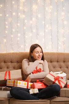 Gelukkige jonge vrouw die vele huidige dozen koestert die gekruiste benen op een kameelbank met met lichten zitten