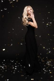 Gelukkige jonge vrouw die verrassend terwijl gouden confettien die vallen kijken