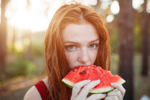 Gelukkige jonge vrouw die watermeloen op de aard eet.