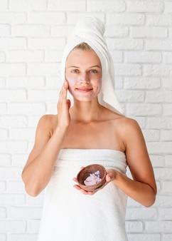 Gelukkige jonge vrouw die witte badhanddoeken op hoofd draagt die kuuroordprocedures doen die gezichts scrub toepassen