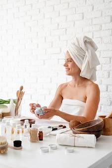 Gelukkige jonge vrouw die witte badjassenhanddoeken op hoofd draagt die kuuroordprocedures doen die natuurlijke ingrediënten in kuuroordschoonheidssalon mengen