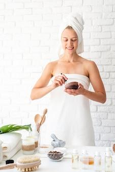 Gelukkige jonge vrouw die witte badjassenhanddoeken op hoofd draagt die kuuroordprocedures doen die natuurlijke ingrediënten in kuuroordschoonheidssalon mengen Premium Foto