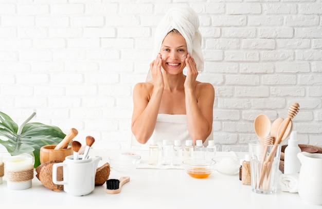 Gelukkige jonge vrouw die witte badjassenhanddoeken op hoofd draagt die kuuroordprocedures in kuuroordschoonheidssalon doen