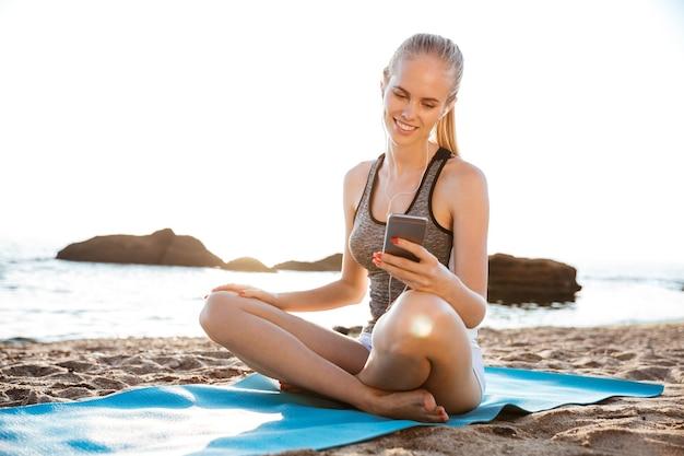 Gelukkige jonge vrouw die yoga doet en een mobiele telefoon gebruikt die buiten op het strand op de mat zit