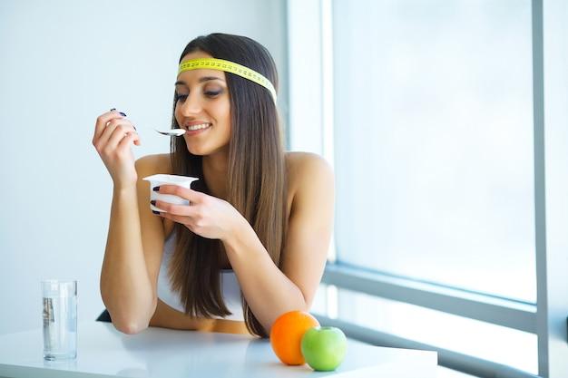 Gelukkige jonge vrouw die yoghurt in keuken eet