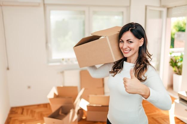 Gelukkige jonge vrouw die zich aan een nieuw huis beweegt.