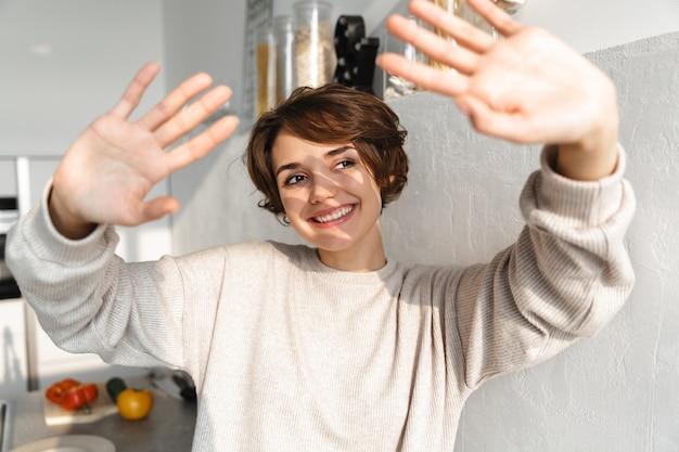 Gelukkige jonge vrouw die zich met uitgestrekte handen bij de keuken bevindt