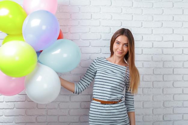 Gelukkige jonge vrouw die zich over bakstenen muur bevindt en ballons houdt.
