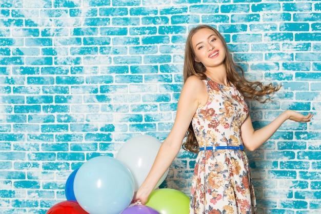 Gelukkige jonge vrouw die zich over blauwe muur bevindt en ballons houdt