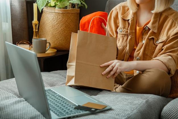 Gelukkige jonge vrouw doet het uitpakken van online kleding bestellen. online winkelen, levering bestellen. het tienermeisje ontspant op bank die aankopen met laptop overweegt.
