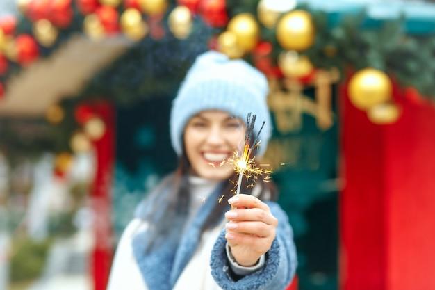 Gelukkige jonge vrouw draagt blauwe jas en geniet van vakantie met bengaalse lichten