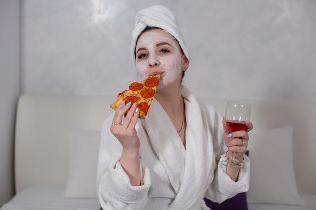 Gelukkige jonge vrouw drinkt rode wijn en eet pizza terwijl ze in bed ligt met een vochtinbrengend masker op haar gezicht foto van hoge kwaliteit