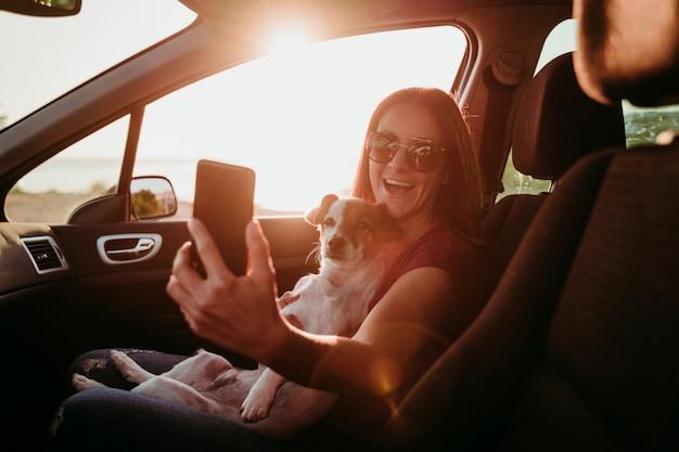 Gelukkige jonge vrouw en haar leuke hond van jack russell in een auto bij zonsondergang. reis concept