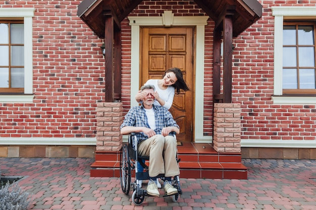 Gelukkige jonge vrouw en haar oom op rolstoel in openlucht. verrassing voor hem.