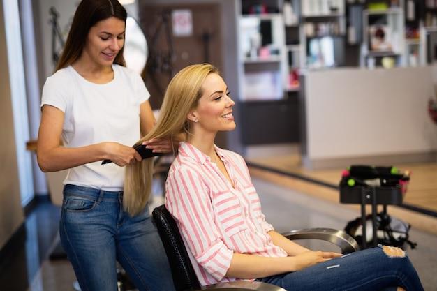 Gelukkige jonge vrouw en kapper met ventilator die hete styling maken bij kapsalon