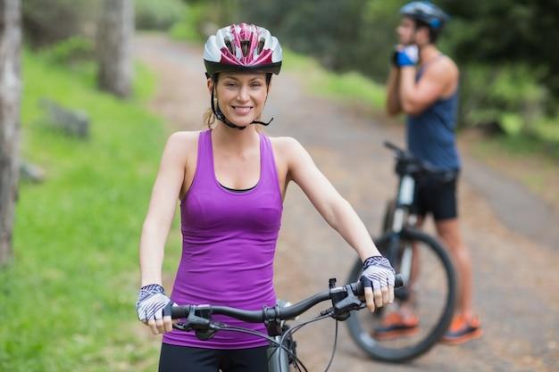 Gelukkige jonge vrouw en man met fietsen op voetpad